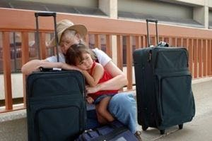 Family sat with their suitcases at Luton Airport